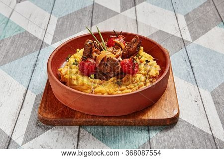 Hummus with beef served in brown bowl. Veal with vegetables closeup view. Meat with tomatoes in deep plate. Restaurant dish serving. Main course portion. Gourmet food shot. Cooking art