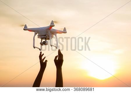 The Uav Drone And Photographer Man Hands.drone Copter Flying With Digital Camera. Uav Drone With Dig