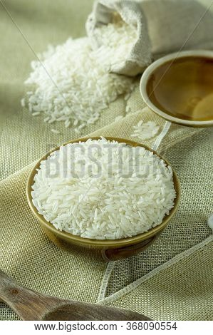 Uncooked Dry Thai Jasmine Rice In Bowl Is Isolated And Burlap Bag With Lid Of Bowl, Wooden Ladle Put