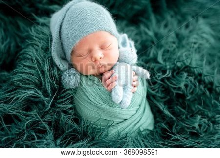 Lovely newborn in green knitted hat wrapped in blanket