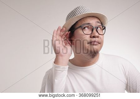 Young Asian Men Wearing Blue Shirt Listen Whispers With Funny Face. Curious. Intently Listen In On J