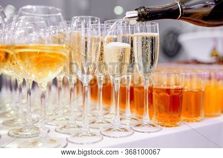 The Bartender Fills A Glass Of Chilled Champagne Into Crystal Glasses On Thin Legs, Which Stand On T