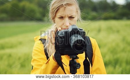 Close-up Of Woman Standing On Spring Grain Field Looking Through Recent Images On Camera, Front View