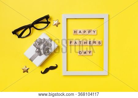 Fathers Day Concept Card On Yellow Background. Gift Box, Mustache, Glasses, Frame And Wooden Letters