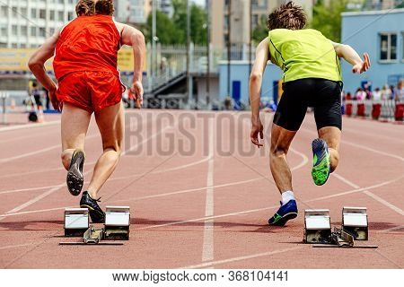 Two Runners Athletes Start From Starting Blocks For 100 Meters Race