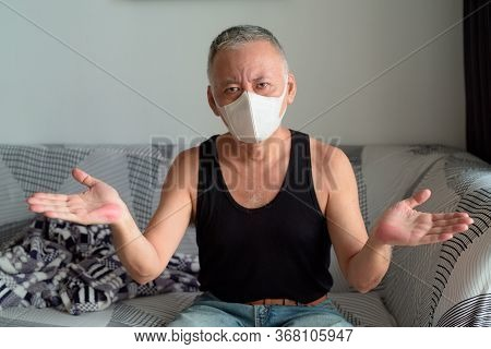 Mature Japanese Man With Mask Shrugging Shoulders At Home Under Quarantine