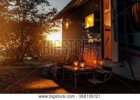 Road Trip Adventures. Calm Warm Night On A Camping. Camper Van, Outdoor Chairs And Romantic Light Fr