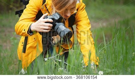Close-up Of Female Photographer Making Macrography Using Dslr Camera Kneeling In Spring Nature