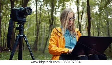 Professional Female Photographer Sitting In Green Leafy Forest Using Laptop Backuping Footage