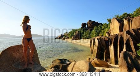 Woman looks at the beach Anse Source d'Argent with big granite rocks at sunset. La Digue Island, Indian Ocean, Seyshelles. Vacations concept.