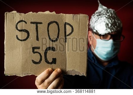 Strange man in a foil hat with a poster Stop 5G. Coronavirus fake news and conspiracy theories