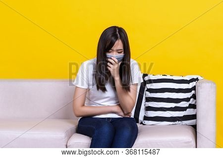 Asian Woman Sitting On Sofa Wearing Protective Face Masks Coughing Or Sneezing. Sick Woman With Flu
