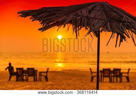 Tropical Sunny Beach Party At Sunset With Sun Umbrellas And Lounge Chairs In Goa, India.