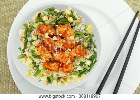 Plate of Harissa Chicken with asparagus, almonds, chicken, rice, squash and apricots.