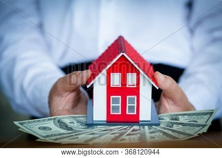 Business People Holding Banknotes There Is A Red Roof House In The Banknote. Real Estate Investment