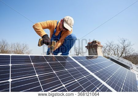 Male Engineer Installing Stand-alone Solar Photovoltaic Panel System Using Screwdriver. Electrician