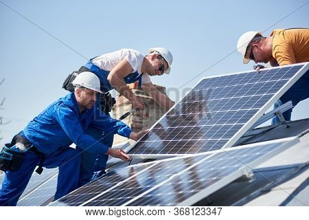 Male Team Engineers Installing Stand-alone Solar Photovoltaic Panel System. Electricians Mounting Bl