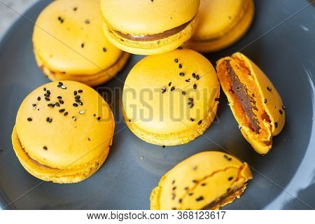Macaroons On A Plate On A Gray Background. French Macarons Isolated. Selective Focus. Beautiful Yell