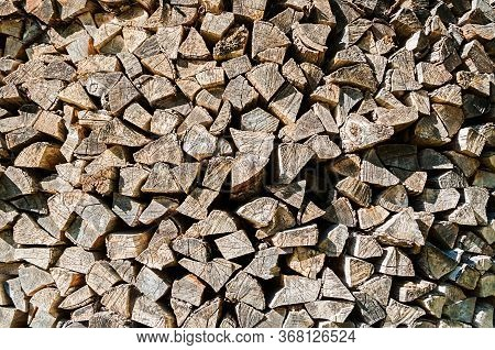 Wooden background with pile of stacked firewood prepared for fireplace and boiler, texture wooden background, pile of firewood, closeup of firewood pile