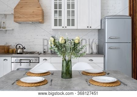Cozy Kitchen At House With Modern Interior, Table Setting In Dining Room, Wooden Cabinets, Gas Stove