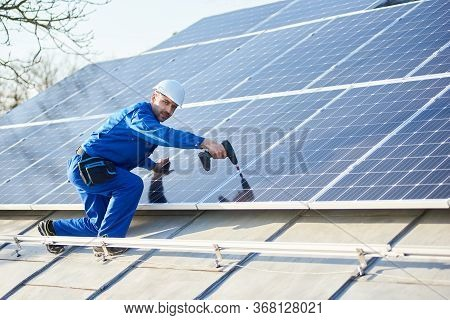 Male Worker In Blue Suit And Protective Helmet Installing Solar Panel System Using Screwdriver. Elec