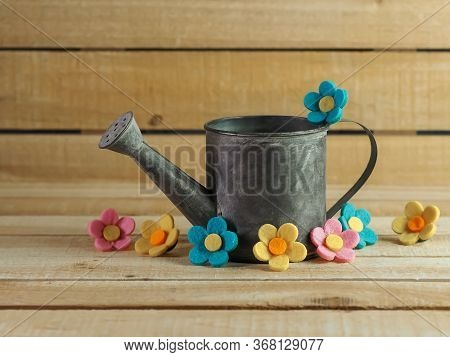 Rustic Metal Watering Can Surrounded By Felt Flowers On A Real Wood Background.  Pink, Yellow And Bl
