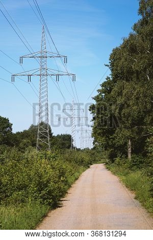 Transmission Line Or Overhead Power Cable With Electricity Pylons Along Rural Dirt Track Country Lan