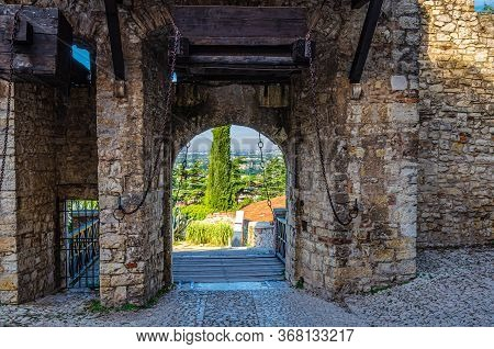 Brescia, Italy, September 11, 2019: Stone Wall With Merlons And Drawbridge Gate Of Medieval Castle O