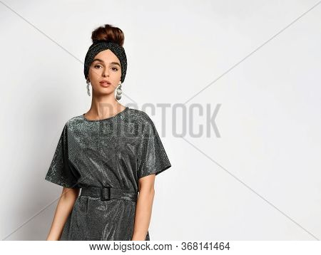 Charming Model With Hair Styled In Updo Posing In Original Headband, Elegant Earrings And Charcoal D