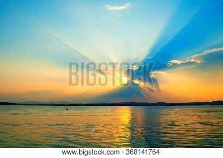 Sea sunset landscape. Summer sunny water scene in picturesque tones. Sea summer nature with mountains at the horizon - panoramic sea view