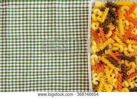 Tricolore Fusilli, Raw Italian Pasta In Plastic Container, Close Up Isolated In Rustic Composition