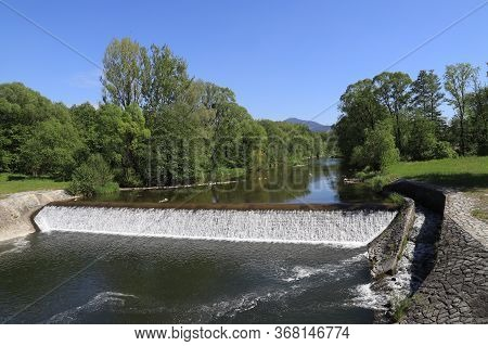 Weir On The Watercourse Of The River Ostravice, In The Background Lysa Hora On A Background Of Blue