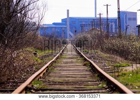 Straight Train Rail Track Going To Old Blue Factory In An Deserted And Polluted Industrial Area