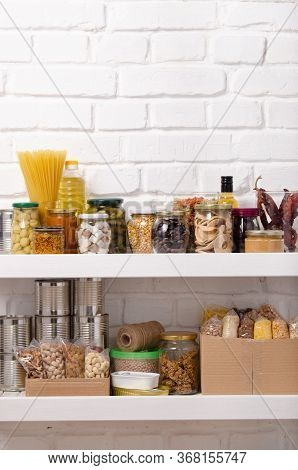 Set Of Long Storage Term Foods On Pantry Shelf Prepared For Disaster Emergency Conditions On Brick W