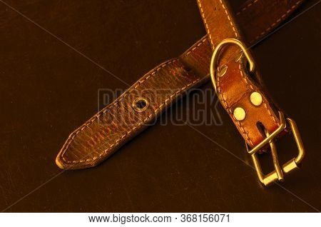 Old Red Leather Dog Collar. A Close-up Of A Shabby And Cracked Dirty Collar On A Dark Table. Love To