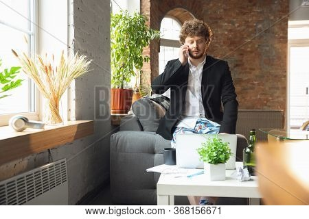 Talking On Phone. Man Without Pants But In Jacket Working On A Computer, Laptop. Remote Office Durin