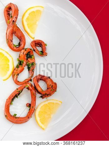 Fresh Squid Grill Sliced With Lemon, Calamari Rings On White Plate On Burgundy Background. Selective