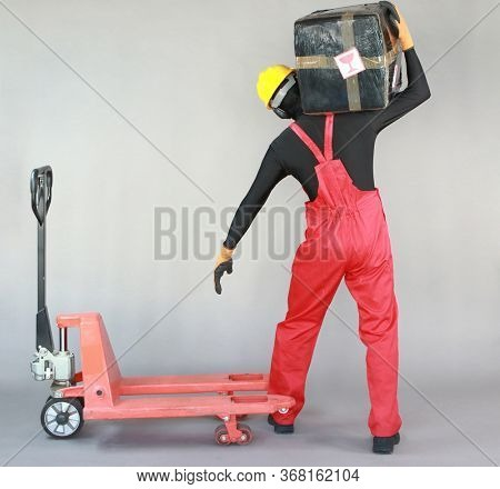 Back view of anonymous worker dealing with heavy package at manual pallet truck.Correct body position.