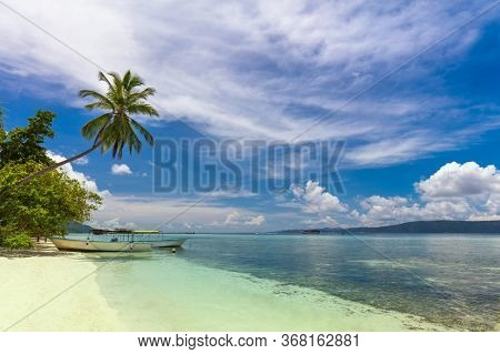 Tropical island beach with white sand, turquoise water and coconut palm,  local boats on island coast, beautiful sky with clouds. Indonesian islands