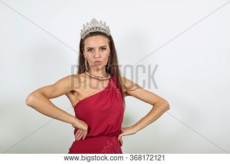 Young Attractive Brunette Woman In Red Stylish Dress, With A Crown On Head On White Background, Prof