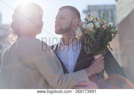 Portrait Of Happy Bride And Groom In Front Of Sun Rays. Bride Kisses The Groom. Smiling Young People