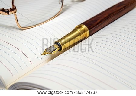 Gilt Pen And Glasses Rests On Open Notebook For Notes Or Writing Text