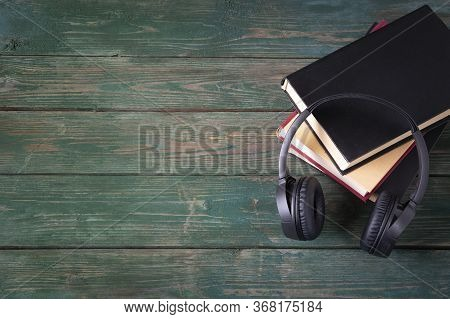 The Concept Of Audiobooks. Headphones And Hardcover Books With A Blank Cover On A Wooden Green Backg