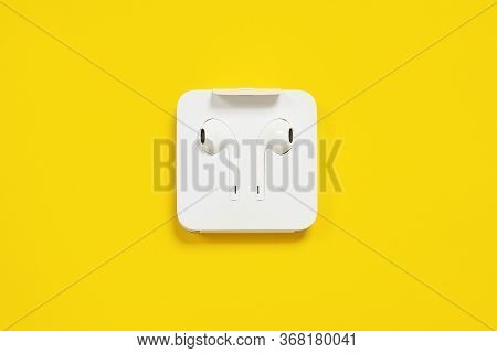 May 01, 2020, Rostov, Russia:  White Wire Earpods In Cardboard Factory Packaging, On Bright Yellow B