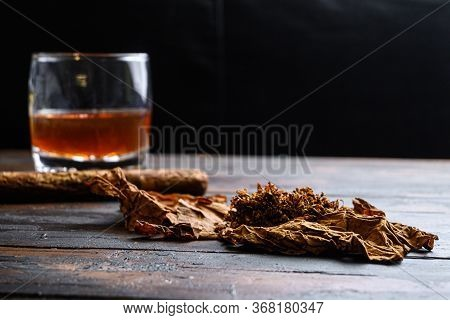 Dried Tobacco Leave And Cut Tobacco With Cigar And Whiskey Rum On Wood Background On Vintage Dark Ta