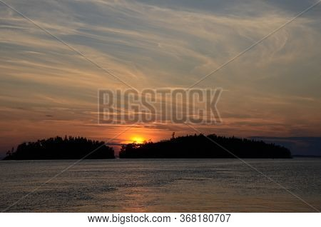 Beautiful Sunset On The Lake And Islands. The Sun Hid Behind The Islands Covered With Forest. Cirrus