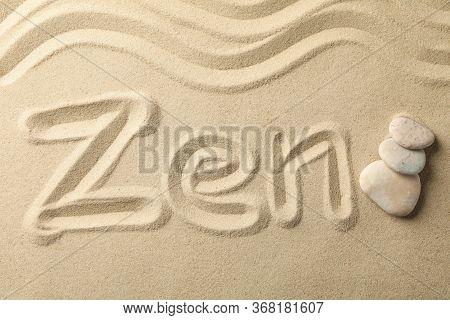 Inscription Zen And Stones On Sand Background. Zen Concept