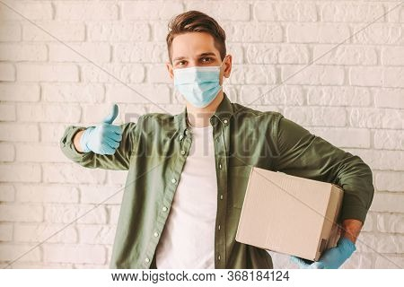 Happy Hipster Man Courier In Medical Face Mask Showing Thumb Up Sign Gesture And Hold Cardboard Box