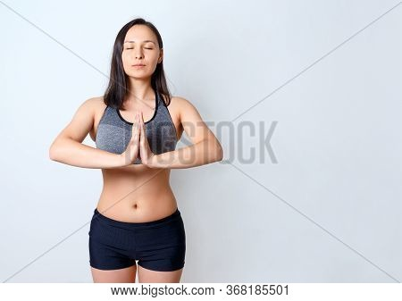 Portrait Of A Calm, Happy Woman On A Blue Background, Meditating With Her Hands Folded On Her Chest.