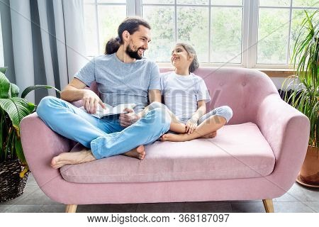 Father And Little Girl Reading A Book, Laughing And Enjoying At Home. Happy Parenthood. Father And D